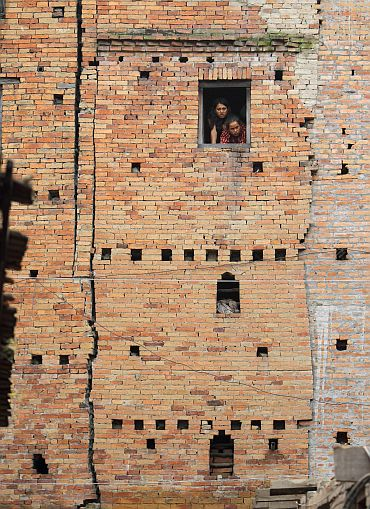 Women look out from the window of a quake-damaged house at Bhaktapur in Nepal