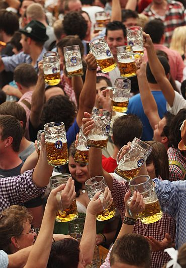 Visitors toast with beer mugs during the opening day of the Oktoberfest 2011 beer festival