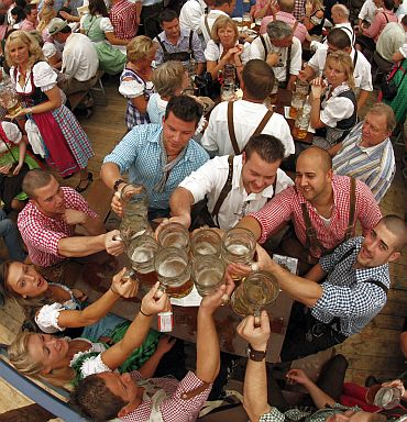 Revellers salute with traditional 1-litre beer mugs at the opening of the Munich Oktoberfest