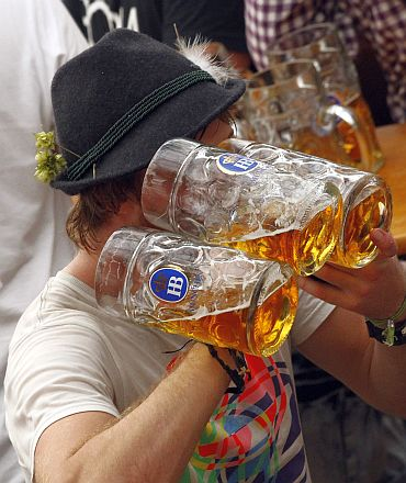 A reveller drinks beer during the first day of the Munich Oktoberfest