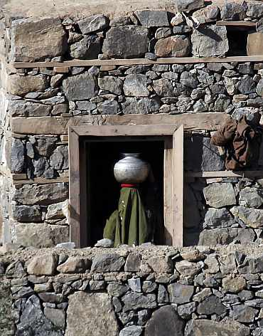 A woman carries a jar of water inside a house, as seen from a bunker of US soldiers in Ghaziabad district in Kunar province, eastern Afghanistan