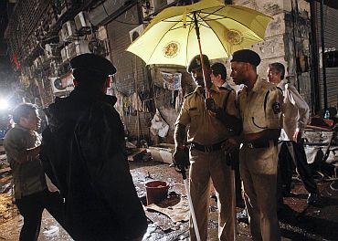 Policemen stand guard at the site of an explosion near the Opera House in Mumbai