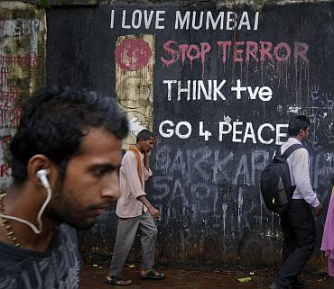 Pedestrians walk past graffiti that outside a Hindu crematorium in Mumbai