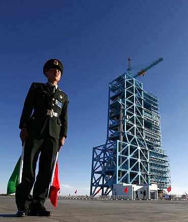 Chinese soldier stands beside Long March II-F rocket loaded with China's unmanned space module Tiangong-1 at the launch pad in the Jiuquan Satellite Launch Center, Gansu province September 28