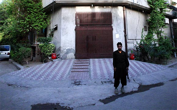 A private security guard stands outside the residence of Hafiz Saeed in Lahore