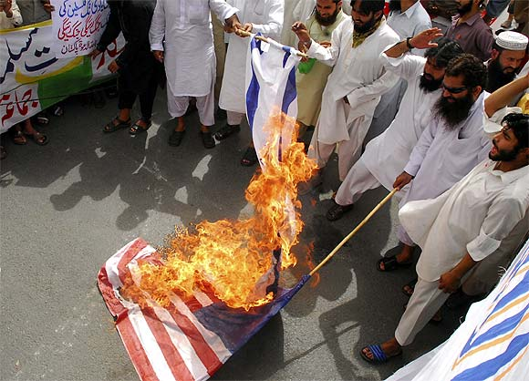Supporters of Jamaat-ud-Dawa set fire to Israeli and US flags during a protest rally