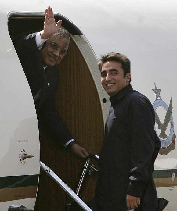 Pakistan's President Zardari waves as his son Bilawal looks on before they depart for Jaipur at the Delhi airport