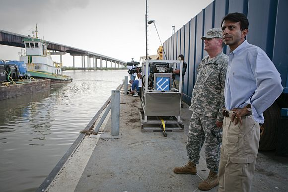 Governor Bobby Jindal looks on as barges loaded with vacuums to clean oil from Deepwater Horizon spill depart marina in Louisiana