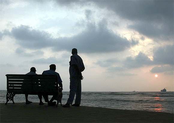 Private security guards sit on a seaside promenade after they evacuated beach-goers after the government announced a tsunami alert in Kochi