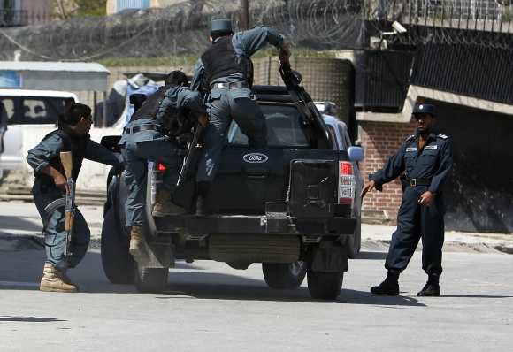 Armed Afghan police climb onto the back of a vehicle after gunmen launched multiple attacks in Kabul
