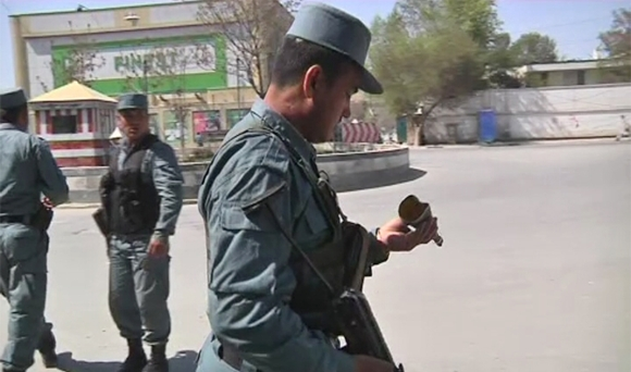 A member of the Afghan security force looks at a piece of debris from a rocket propelled grenade which was found after gunmen launched multiple attacks in Kabul