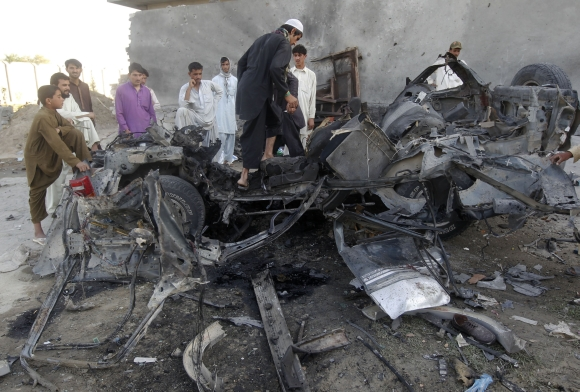 Afghan men stand around the wreckage of a car used by a suicide attacker in Jalalabad province