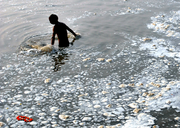 A devotee takes a dip in the polluted Sangam, confluence of three rivers, the Ganga, the Yamuna and Saraswati