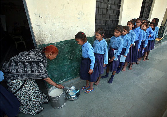 Children stand in line to collect their free mid-day meals in school