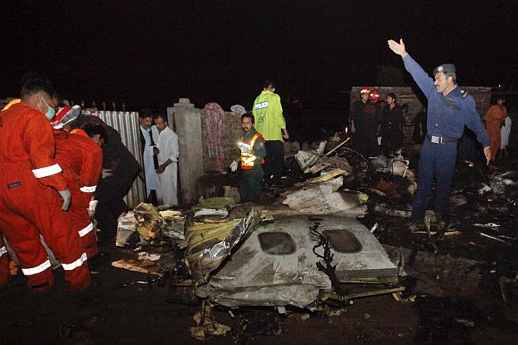 Police and rescue workers go through the wreckage