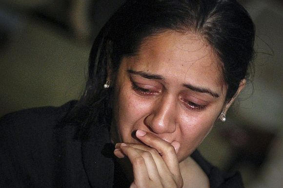 A relative of a victim of the Bhoja Air airliner crash mourns at the Jinnah International Airport