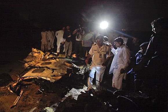 Aviation officials stand next to the wreckage of the Boeing 737 airliner