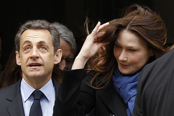France's President Sarkozy leaves a polling station with his wife Carla Bruni-Sarkozy after voting during the first round of 2012 French presidential election in Paris
