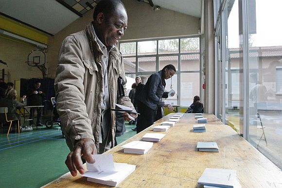 French citizens select ballots with the names of candidates at a polling station in the first round of the 2012 French presidential election in Vaulx-en-Veliln on Sunday