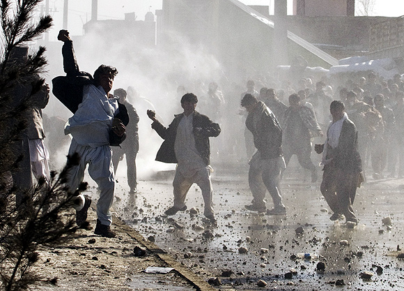 Afghan men throw rocks towards a water canon near a US military base in Kabul to protest the burning of the Quran
