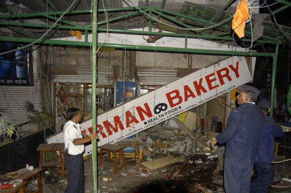 Firefighters examine the site of a bomb blast at the German Bakery restaurant in Pune on February 10, 2010