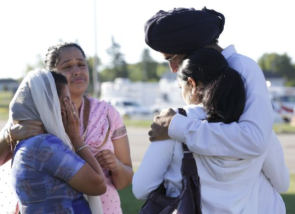 Mourners cry outside the scene of a mass shooting at a gurdwara in Oak Creek, Wisconsin, on Sunday where six people were shot dead.