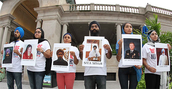 Protestors hold pictures of victims of the shootout at the vigil in New York