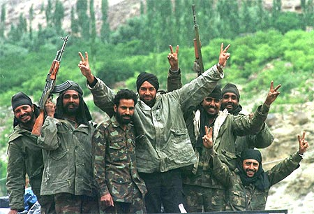 Indian soldiers show the victory signs in Drass after India captured Tiger Hill in northern Kashmir on July 4, 1999