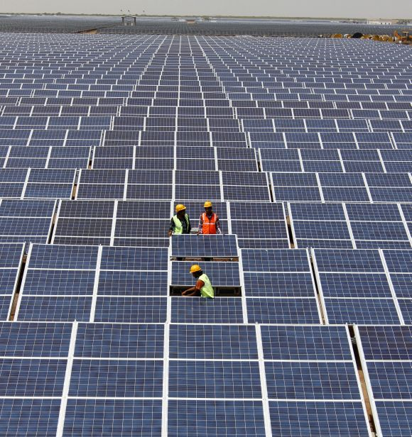 Workers install solar panels at the Gujarat solar park under construction in Charanka village in Gujarat