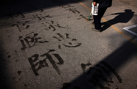 A man writes Chinese characters on a footpath using water and a brush in central Beijing