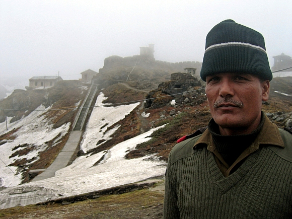 A soldier stands at the 4,310 metre high Nathu-la pass on India's north-eastern border with China. Just a few yards away bulldozers on both sides of the frontline are building not fortifications but a road, to connect India and China and reopen a historic trade route