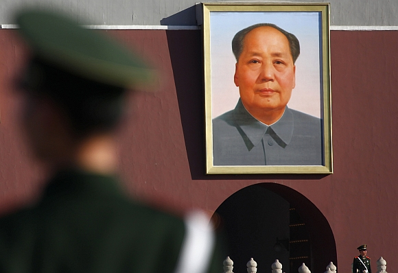 Paramilitary policemen stand guard near the portrait of late Chinese Chairman Mao Zedong facing Tiananmen Square, prior to a plenary session of the National People's Congress in Beijing