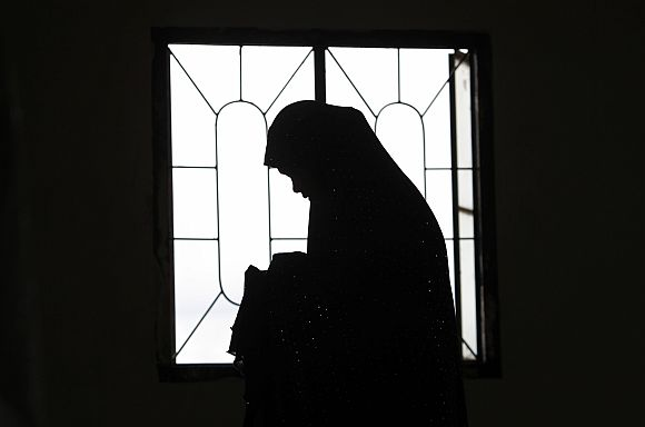 A Muslim woman is silhouetted as their community offers prayers of peace for recent violent protests and attacks in the Islamic world against the US, at a mosque in Marikina City