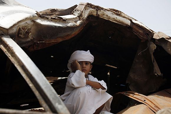 A boy takes shelter from the sun in the wreckage of a car destroyed during recent violence as he attends a rally to demand the ouster of Yemen's President Ali Abdullah Saleh in the southern city of Taiz