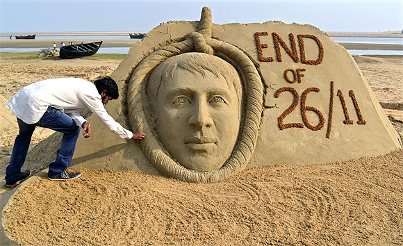 Indian sand artist Sudarshan Patnaik gives the final touches to a sand sculpture of Mohammad Ajmal Kasab on a beach in Odisha