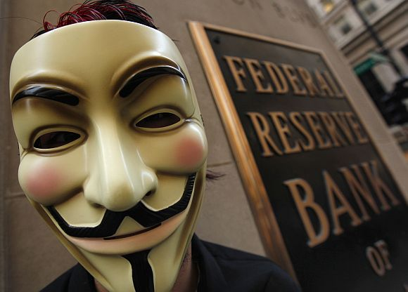 A protestor demonstrates in support of the New York Occupy Wall Street protests in front of the Federal Reserve Bank of Chicago in the city's financial district