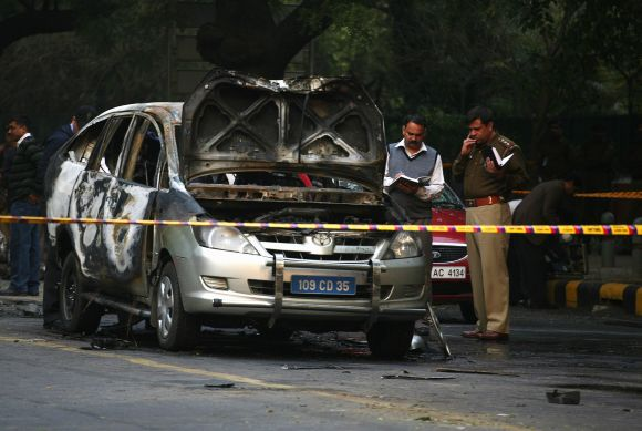 Police and forensic officials examine a damaged Israeli embassy car after an explosion in New Delhi