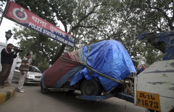 A covered damaged Israeli embassy car is towed away from a police station to another police station in New Delhi