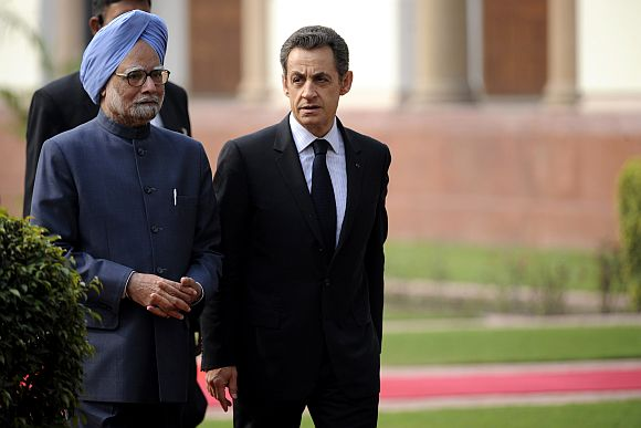 France's President Nicolas Sarkozy walks Prime Minister Manmohan Singh at Hyderabad House in New Delhi