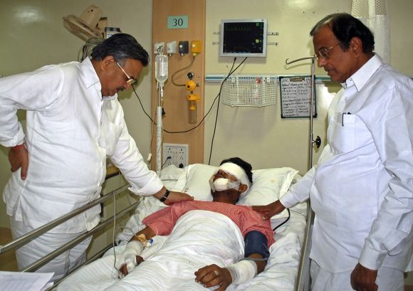 Union Home Minister P Chidambaram and Chhattisgarh Chief Minister Raman Singh stand besides a policeman, who was wounded in a Maoist attack, at a hospital in Raipur