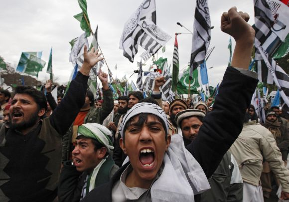 A supporter of a religious and political party chants slogans with hundreds of others during an anti-US rally organized by the Difa-e-Pakistan Council in Islamabad