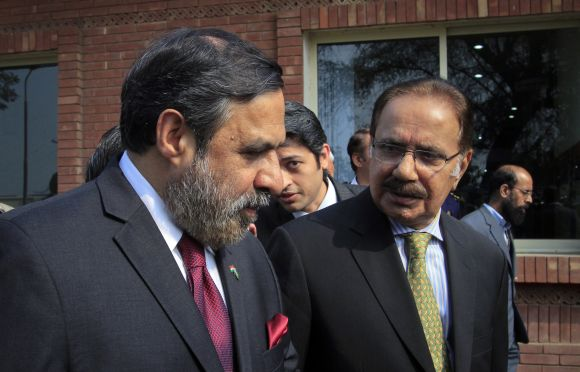 Union Commerce Minister Anand Sharma talks with his Pakistani counterpart Makhdoom Amin Fahim after crossing into Pakistan, to meet at the Wagah border post, near Lahore, on February 13