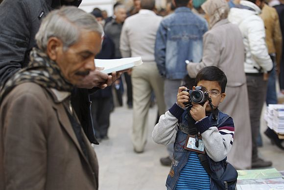 Hashim, 8, takes pictures at al-Mutanabi street in Baghdad
