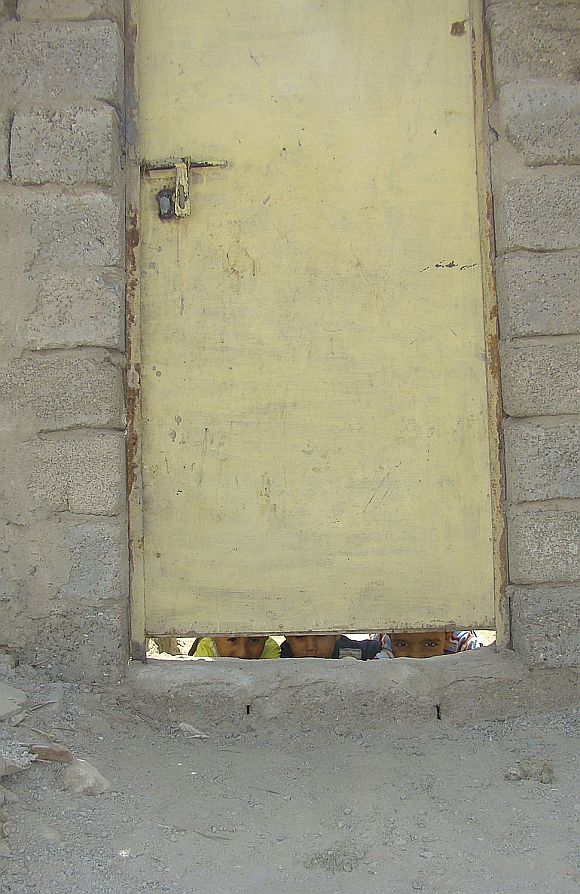 Children peek out from the doorway of their makeshift house in the city of Kut, 150 km (95 miles) southeast of Baghdad in this 2009 photo