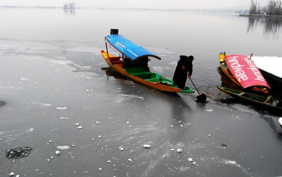A boatman tries to steer his shikara through a semi-frozen Dal Lake in Srinagar