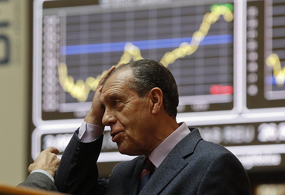 A man holds his head at the bourse in Madrid. European stock futures pointed to a weaker open for equities on Monday as political uncertainties in highly-indebted Italy and Greece raised fresh concerns that the region's debt crisis would intensify and threaten a fragile global economic recovery.