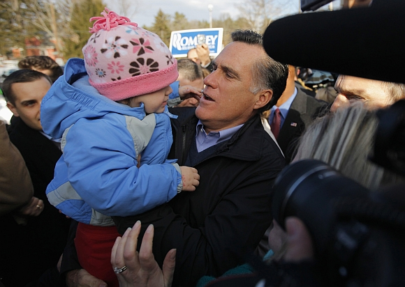 Romney holds a child while visiting a polling station in Manchester, New Hampshire