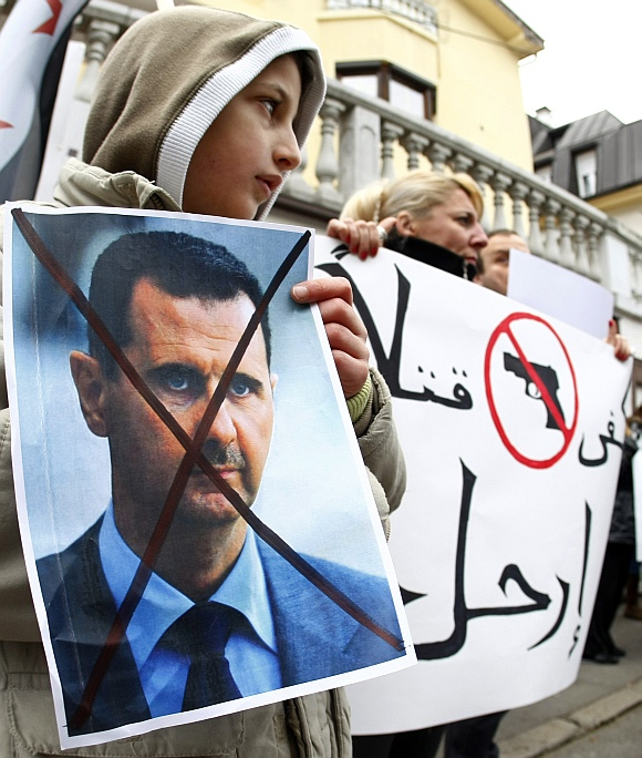 A Syrian holds a poster of Syrian President Bashar al-Assad during a protest against his regime