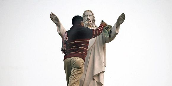 A worker cleans the statue of Jesus in New Delhi