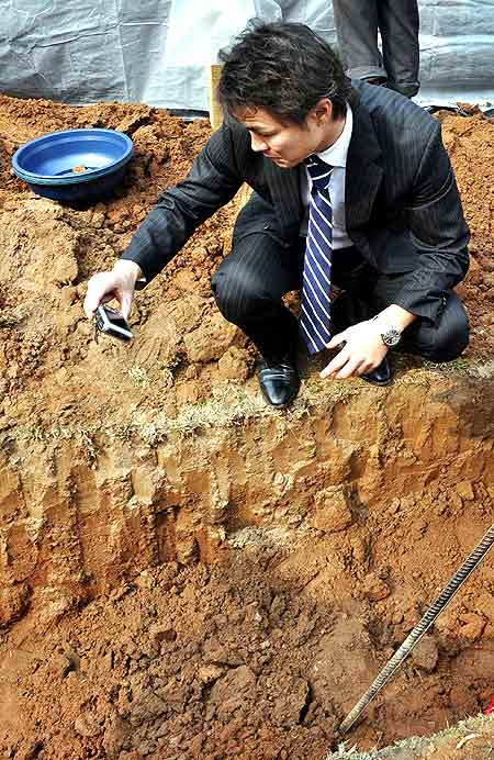 An official photographs one the dug up graves